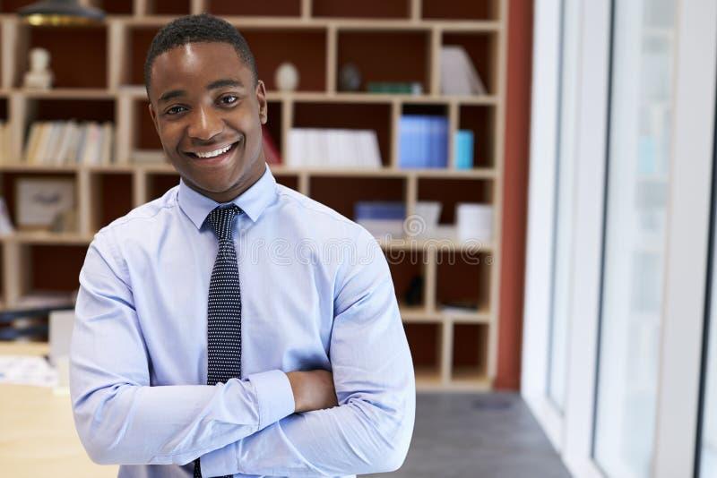 Giovane uomo d'affari nero che sorride alla macchina fotografica in una sala del consiglio fotografia stock