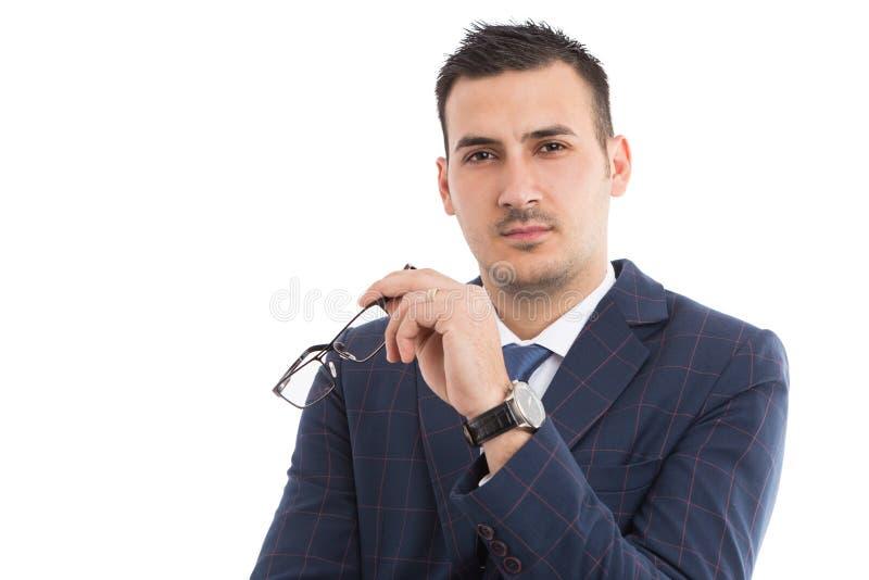Giovane uomo d'affari o insegnante che tiene i vetri fotografia stock