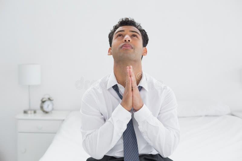 Giovane uomo d'affari premuroso che si siede sul letto fotografia stock libera da diritti