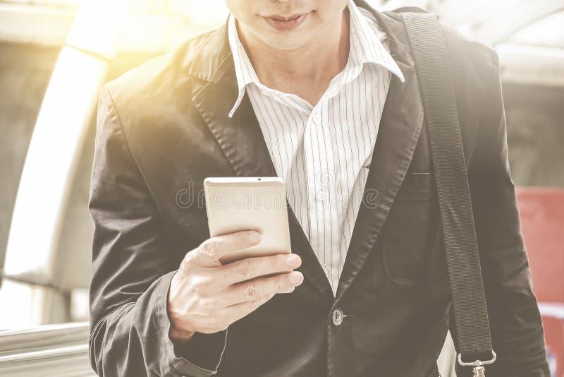 Giovane uomo d'affari professionale urbano che per mezzo dello Smart Phone Smartphone mobile della tenuta dell'uomo d'affari face immagini stock
