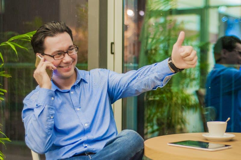 Giovane uomo d'affari rilassato allegro che mostra gesto giusto e che parla sul telefono cellulare in caffè fotografia stock libera da diritti