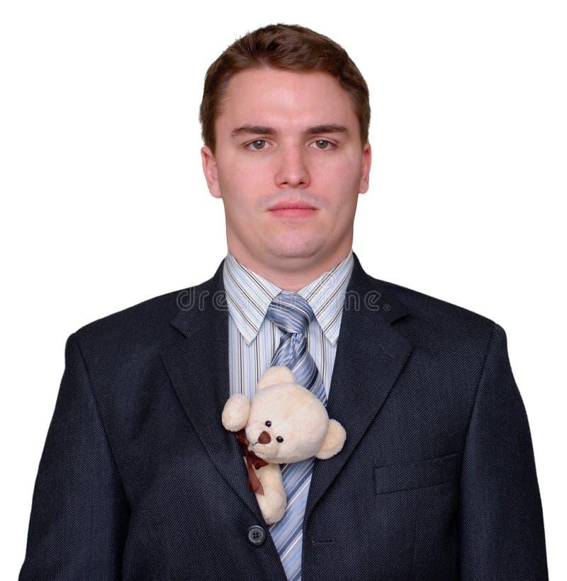 Giovane uomo d'affari serio con l'orso dell'orsacchiotto in vestito fotografia stock libera da diritti