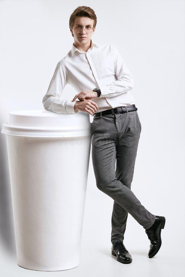 Giovane uomo d'affari sicuro in camicia che posa con una tazza di caffè gigante fotografia stock