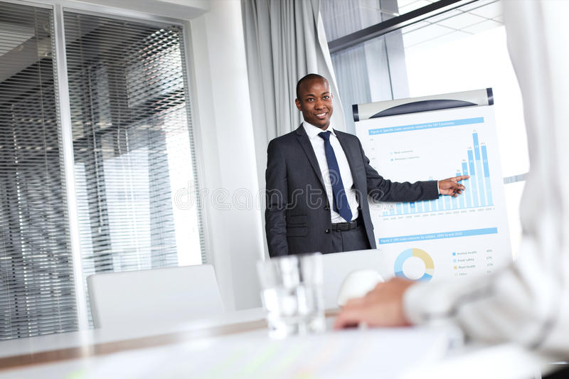 Giovane uomo d'affari sicuro che indica verso il grafico mentre dando presentazione in ufficio fotografie stock libere da diritti