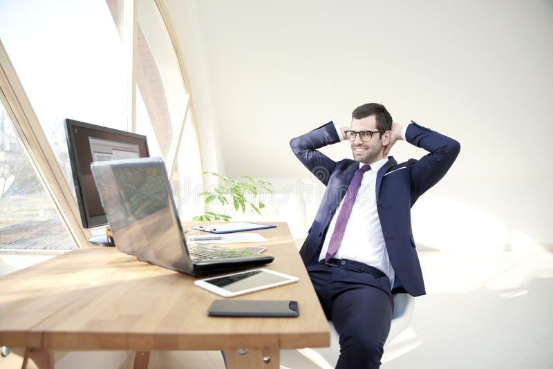 Giovane uomo d'affari sicuro che si rilassa alla scrivania fotografia stock libera da diritti
