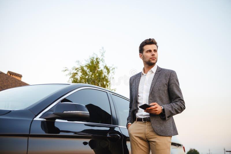 Giovane uomo d'affari sicuro in vestito che sta alla sua automobile fotografie stock libere da diritti