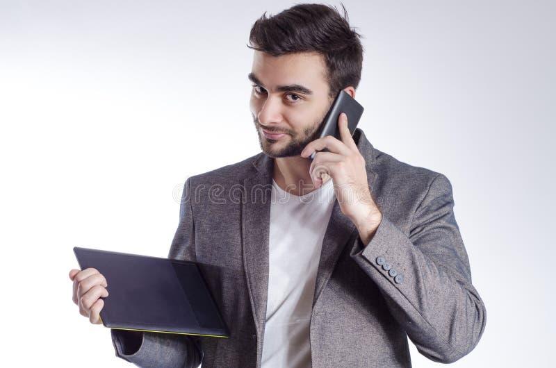 Giovane uomo d'affari soddisfatto che parla sul telefono cellulare immagine stock