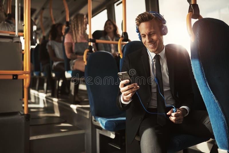 Giovane uomo d'affari sorridente che ascolta la musica sul suo comm di mattina fotografia stock