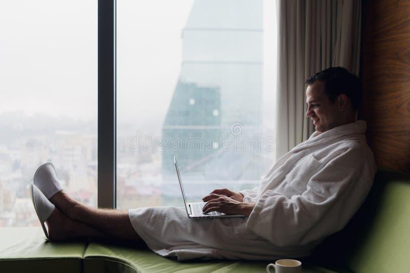 Giovane uomo d'affari sorridente che lavora all'accappatoio bianco d'uso del computer portatile che si siede vicino alla finestra fotografie stock