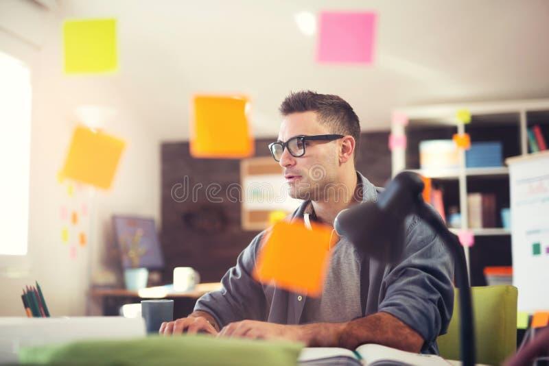 Giovane uomo d'affari sorridente che lavora nell'ufficio immagine stock libera da diritti