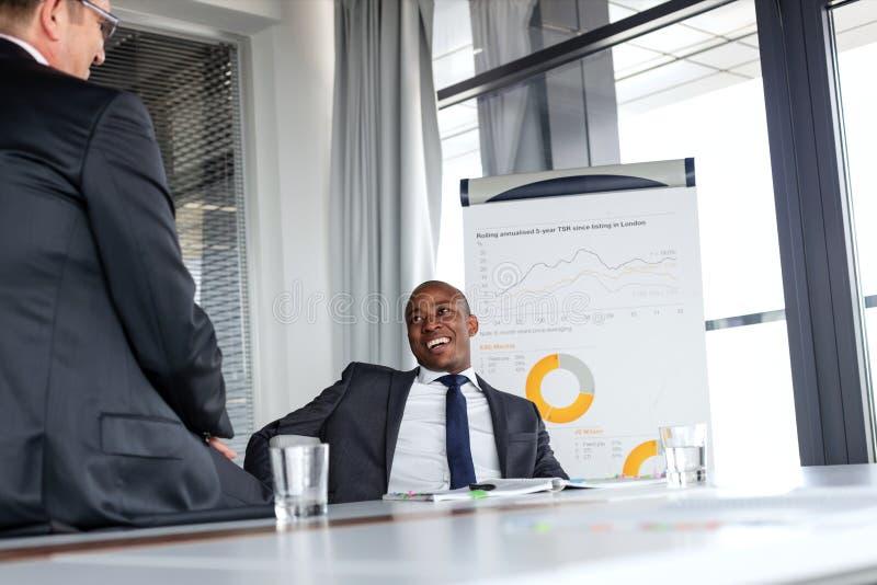 Giovane uomo d'affari sorridente che parla con il collega maschio nella sala riunioni immagini stock libere da diritti