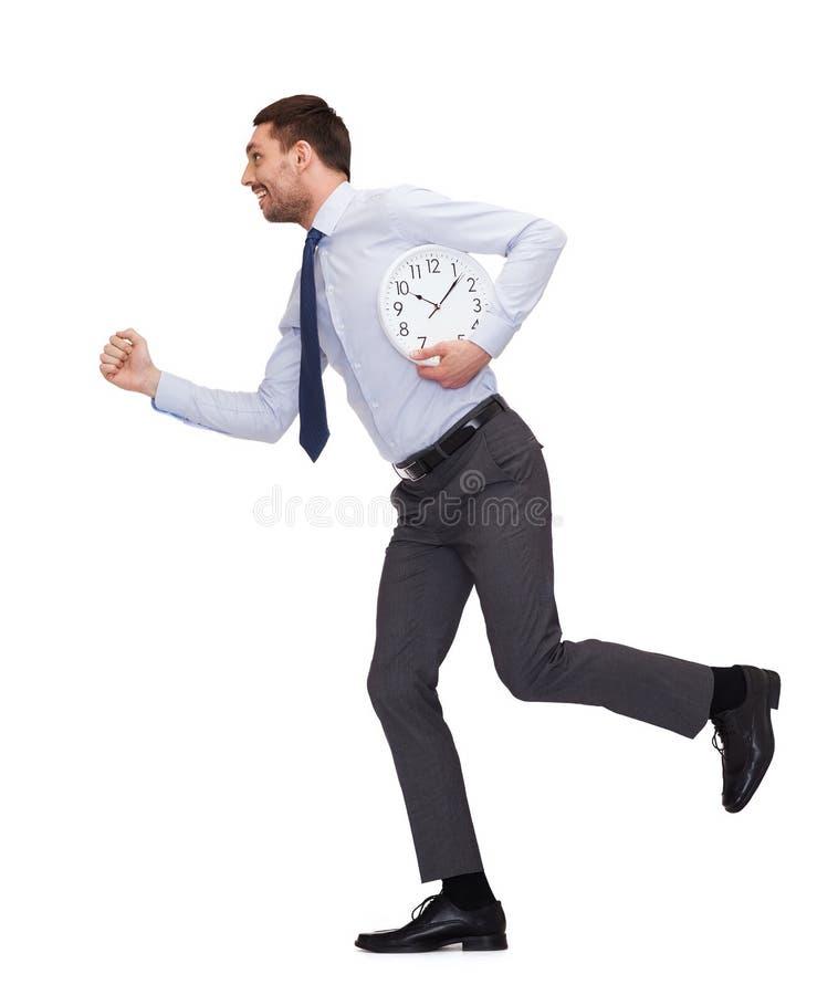 Giovane uomo d'affari sorridente con funzionamento dell'orologio immagini stock