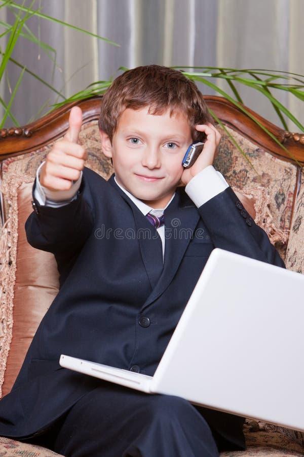Giovane uomo d'affari sorridente con il calcolatore che mostra bene fotografie stock libere da diritti