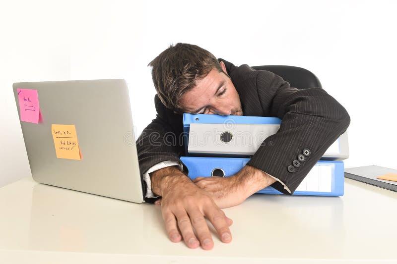 Giovane uomo d'affari stanco e sprecato che lavora nello sforzo al sonno del computer portatile dell'ufficio esaurito fotografia stock libera da diritti