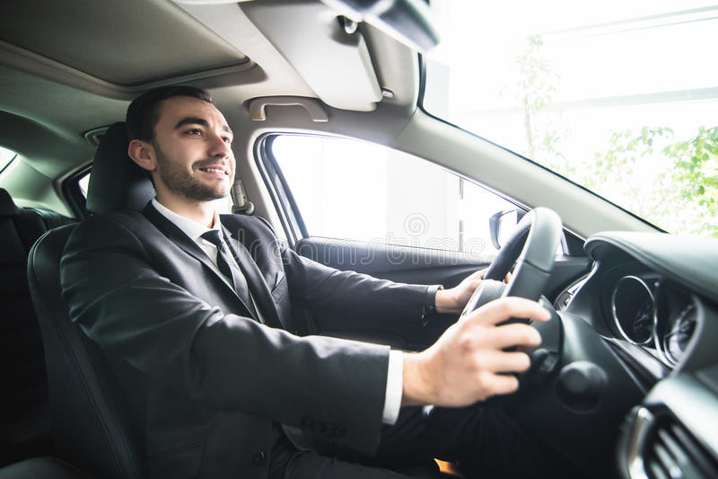 Giovane uomo d'affari in sua automobile Autista dell'automobile luxuty Automobile bella dell'azionamento dell'uomo fotografie stock