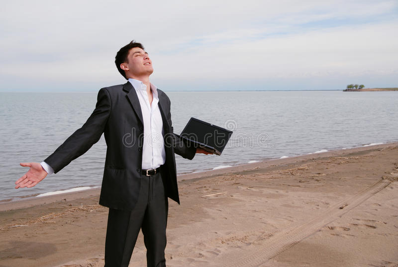 Giovane uomo d'affari sulla spiaggia immagini stock