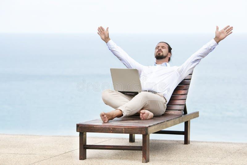 Giovane uomo d'affari sulla spiaggia che riposa sul suo sdraio che per mezzo della sua compressa fotografie stock libere da diritti