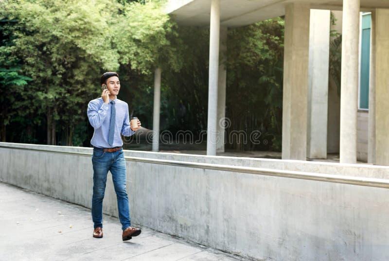 Giovane uomo d'affari Talk di motivazione via Smartphone mentre outd della passeggiata immagine stock libera da diritti