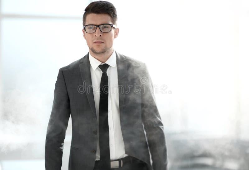 Giovane uomo d'affari in un ufficio fumoso fotografia stock