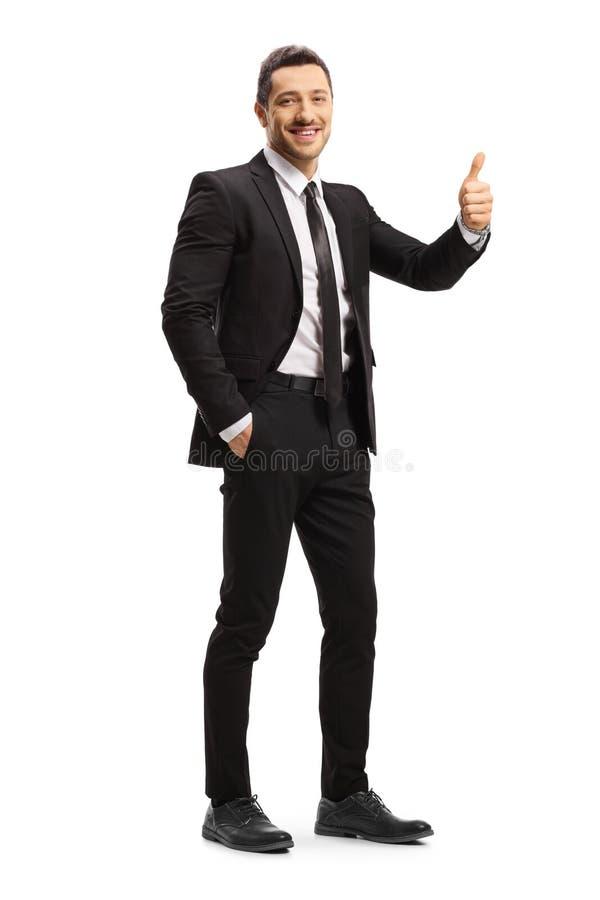 Giovane uomo d'affari in un vestito nero che mostra i pollici su immagini stock