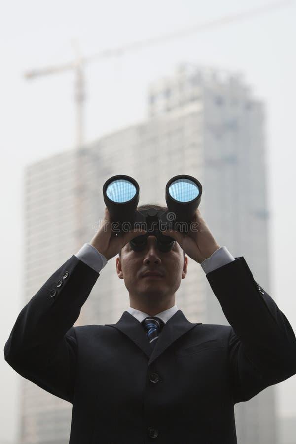 Giovane uomo d'affari Using Binoculars e esaminare la distanza, vista di angolo basso immagini stock libere da diritti