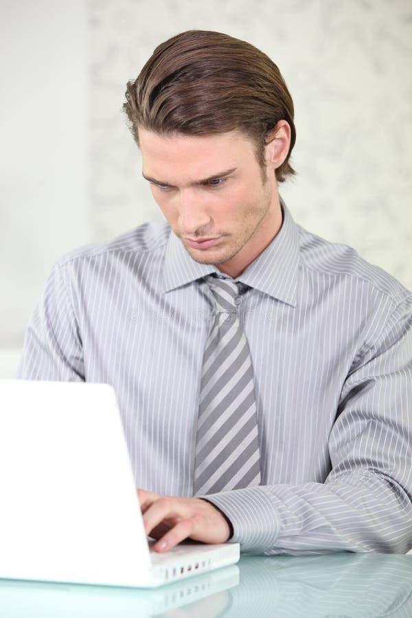 Giovane uomo d'affari in vestito davanti ad un computer portatile immagini stock