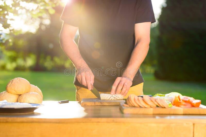 Giovane uomo dei pantaloni a vita bassa che prepara alimento per il partito della griglia del giardino, barbecue di estate fotografia stock