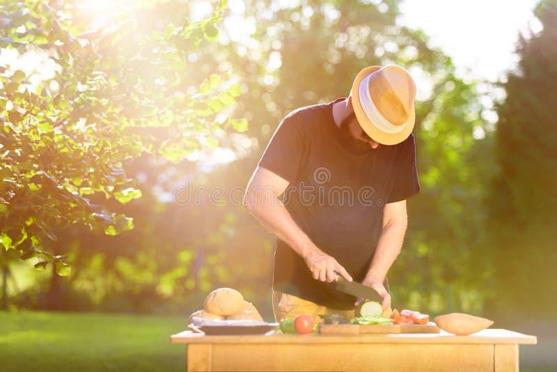 Giovane uomo dei pantaloni a vita bassa che prepara alimento per il partito della griglia del giardino, barbecue di estate immagini stock libere da diritti