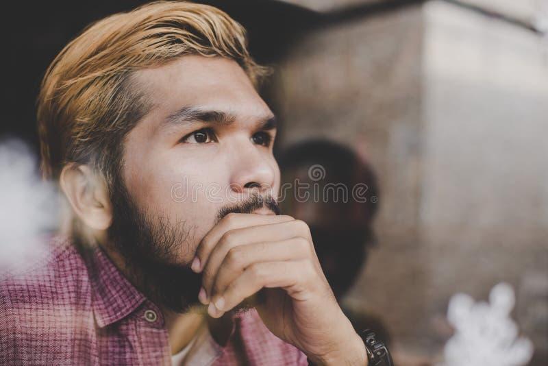 Giovane uomo dei pantaloni a vita bassa che si siede nella caffetteria che pensa e che guarda aw immagini stock