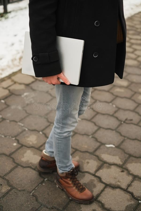 giovane uomo dei pantaloni a vita bassa con il computer portatile a disposizione con uno sguardo urbano in città nell'inverno del fotografia stock libera da diritti