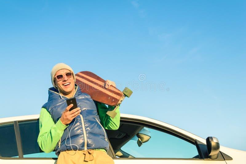 Giovane uomo dei pantaloni a vita bassa con musica e l'automobile dello smartphone fotografia stock