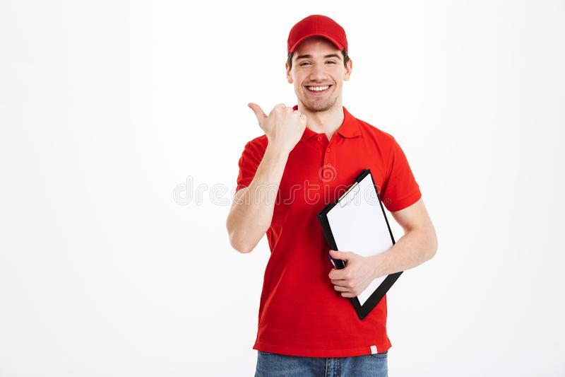 Giovane uomo del corriere in asi sorridente di rosso ed indicante uniforme del dito fotografia stock