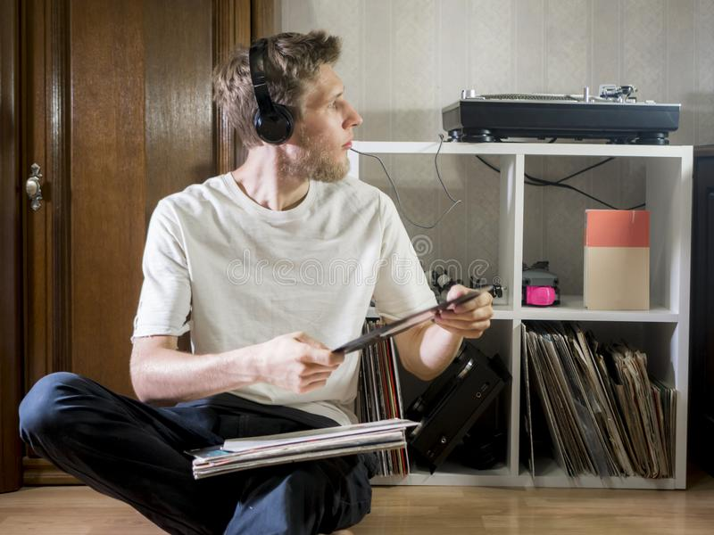 Giovane uomo del mante della musica in casuale e nella seduta a casa in cuffie con i dischi di vinile fotografia stock