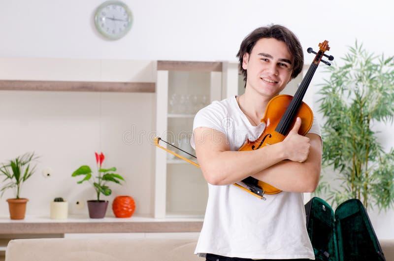 Giovane uomo del musicista che pratica giocando violino a casa immagini stock