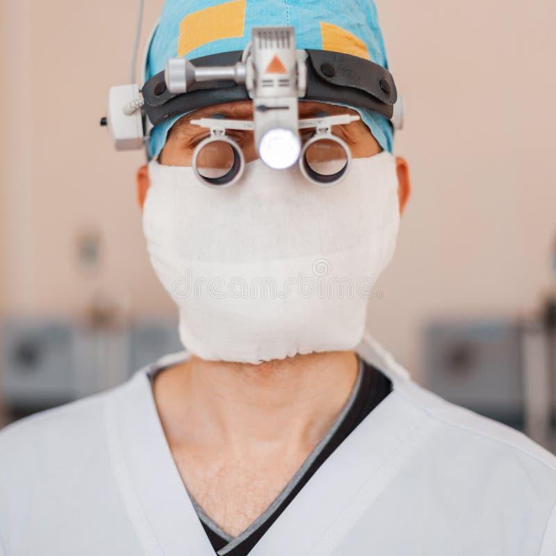 Giovane uomo del neurochirurgo in una maschera medica con le lenti d'ingrandimento professionali con le lenti di ingrandimento bi immagine stock
