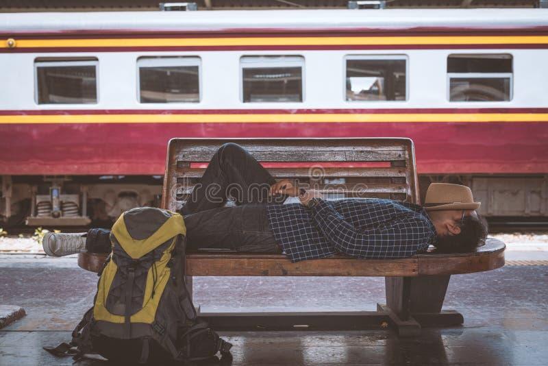 Giovane uomo del viaggiatore che dorme al binario della stazione ferroviaria di Bangkok fotografia stock libera da diritti
