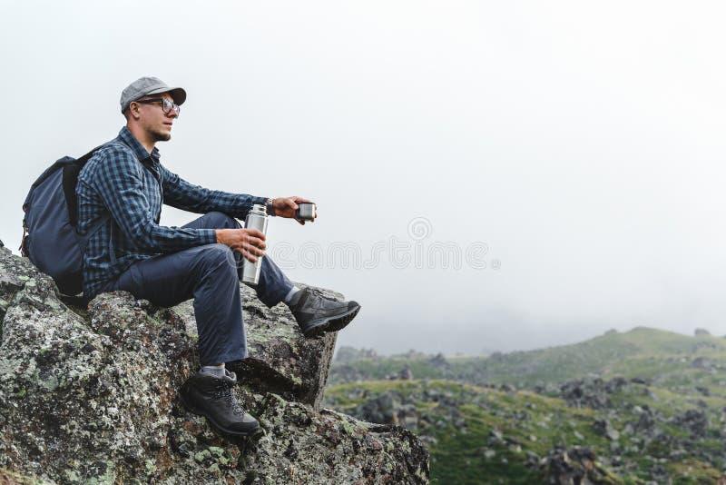 Giovane uomo del viaggiatore che si siede sulla cima e che tiene il termos in sua mano Escursione del concetto di turismo di avve immagini stock libere da diritti