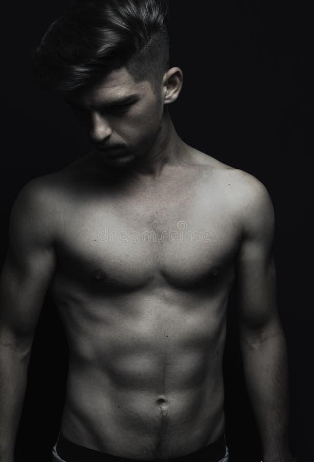 Giovane uomo dell'atleta con il corpo di addominali scolpiti che guarda giù davanti al bl fotografia stock