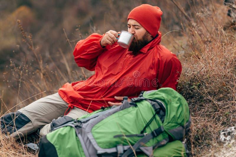Giovane uomo dell'esploratore che beve bevanda calda in montagne, sedentesi e rilassantesi dopo il trekking fotografia stock
