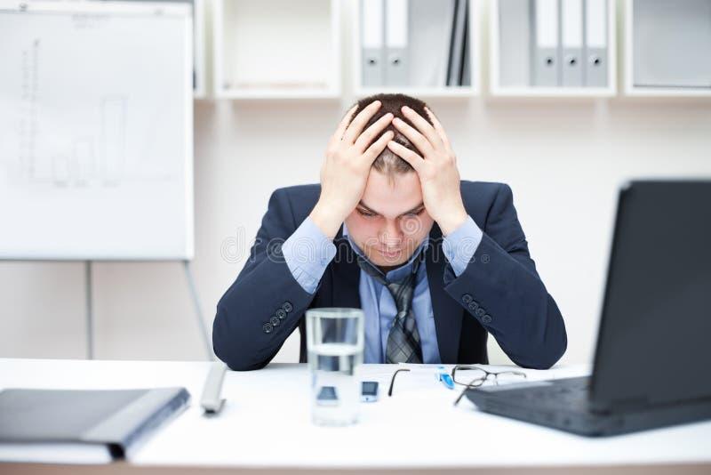Giovane uomo depresso di affari che tiene la sua testa immagine stock
