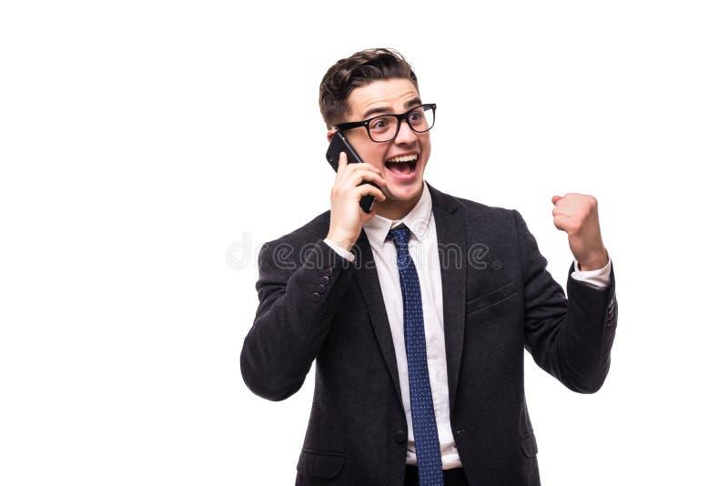 Giovane uomo di affari che parla sul cellulare, eccitato, rallegrandosi, isolato su fondo bianco immagini stock libere da diritti