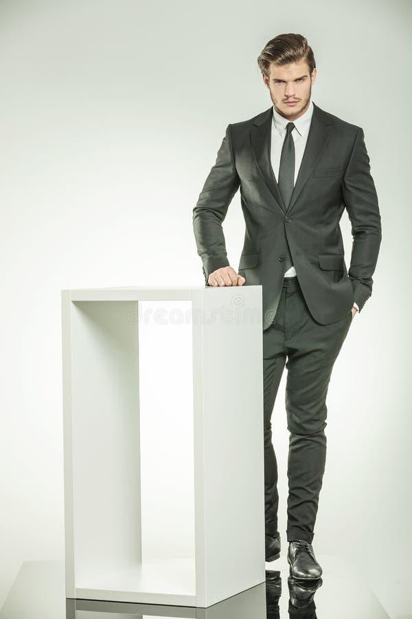 Giovane uomo di affari che posa vicino ad una tavola moderna bianca immagini stock