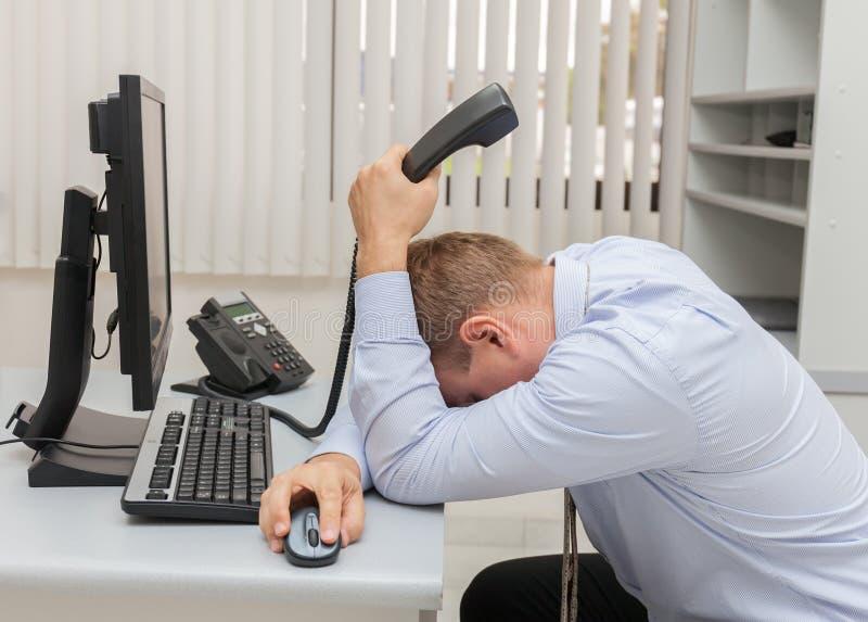 Giovane uomo di affari con i problemi e lo sforzo nell'ufficio che si siede davanti al computer immagine stock