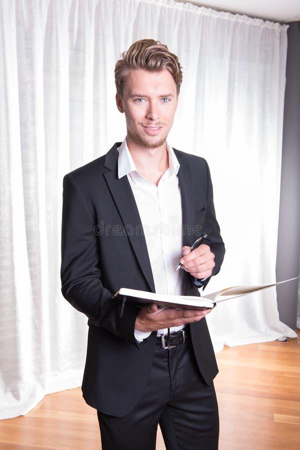 Giovane uomo di affari del ritratto in vestito che prende le note nel libro fotografia stock libera da diritti
