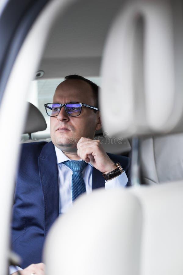 Giovane uomo di affari nel sedile posteriore in un'automobile costosa con un salotto codificato, va ad una riunione immagine stock