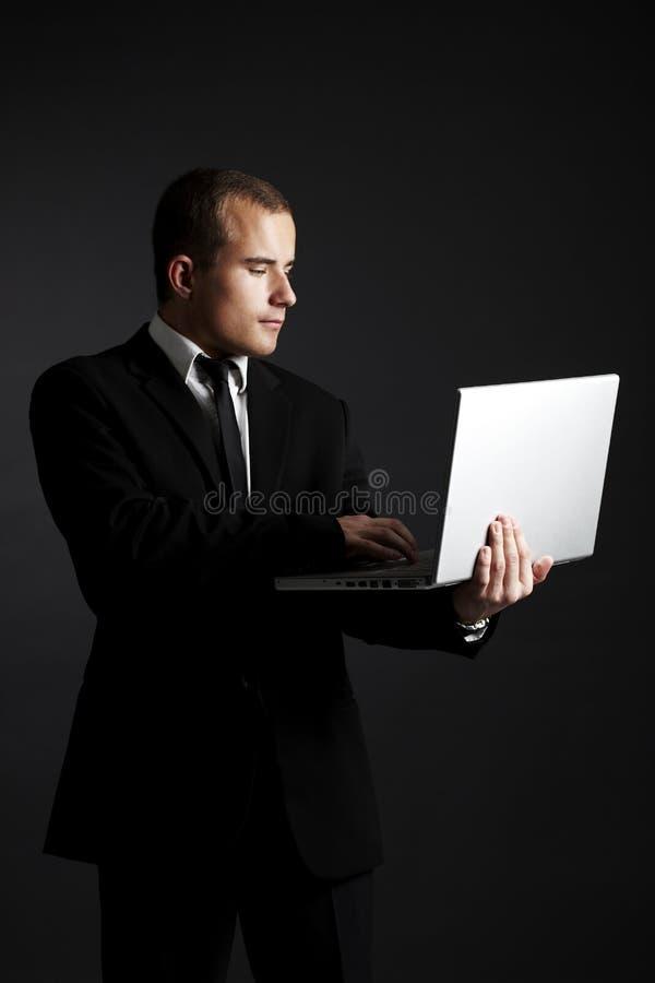 Giovane uomo di affari sul nero con il computer portatile immagine stock