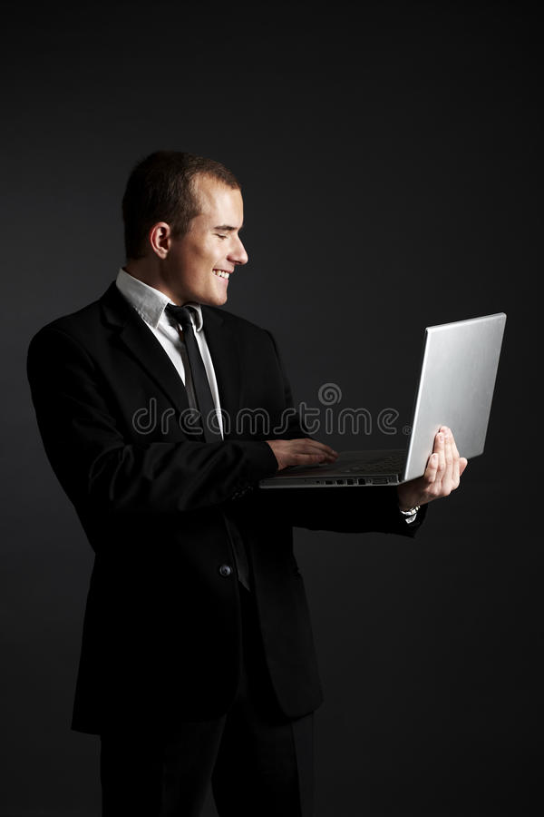 Giovane uomo di affari sul nero con il computer portatile fotografie stock