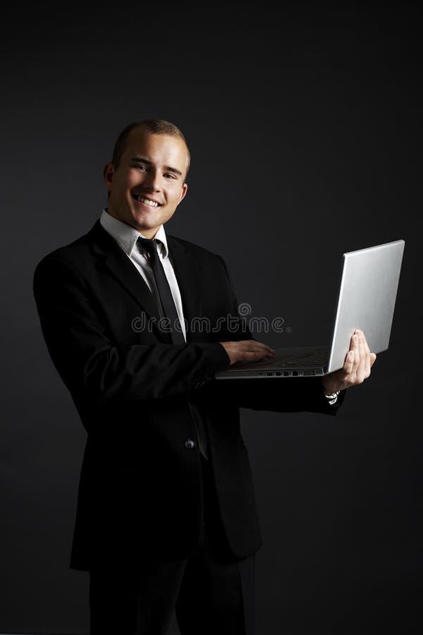 Giovane uomo di affari sul nero con il computer portatile fotografia stock libera da diritti
