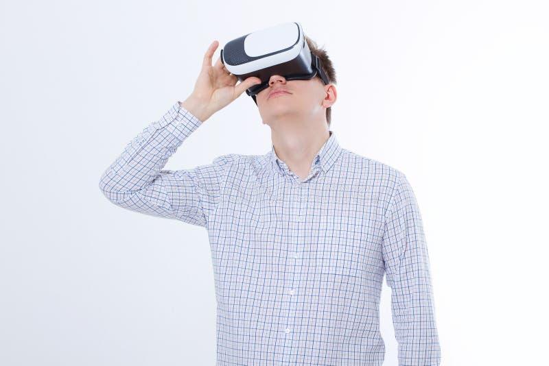 Giovane uomo di affari in vetri del vr, occhiali di protezione guardante realtà virtuale isolati su fondo bianco Copi lo spazio e fotografia stock libera da diritti