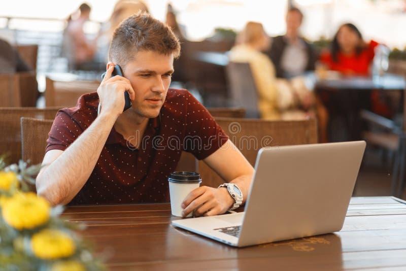 Giovane uomo di blogger con un computer portatile e un caffè che fanno una chiamata fotografia stock